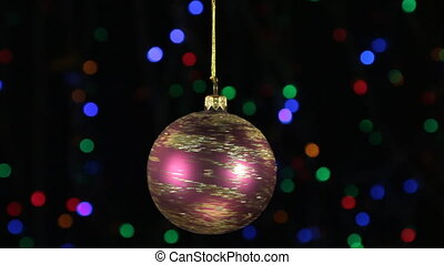 Close-up, the rotation of a red Christmas ball hanged on a...