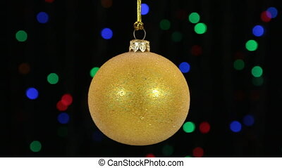 Close-up, the rotation of a yellow Christmas ball hanged on...