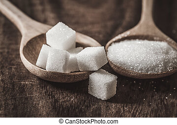 Close up the sugar cubes and cane in wooden spoon on table ,retro color tone