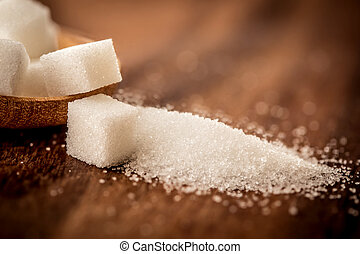 the sugar cubes and cane in wooden spoon on the table ,retro color tone