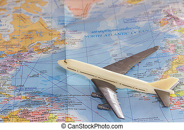Close up the white toy airplane on the world map background.