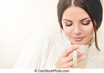 Close up thoughtful young woman smelling the aroma of a coffee drink in a cup