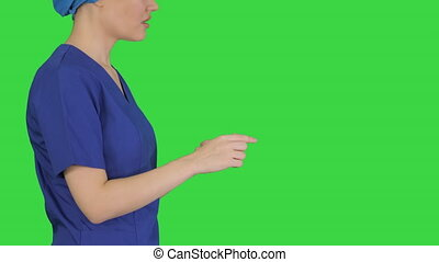 Close up to hands. Side view. Female doctor in blue uniform talking about medical care on a Green Screen, Chroma Key. Professional shot in 4K resolution. 043. You can use it e.g. in your medical, commercial video, business, presentation, broadcast