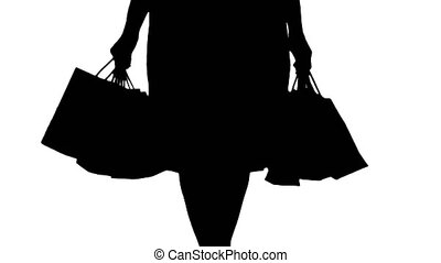 Silhouette After day shopping. Young woman carrying shopping...