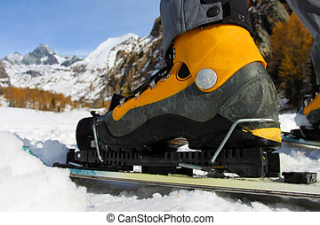 Close up to the ski boot with view towards the mountains