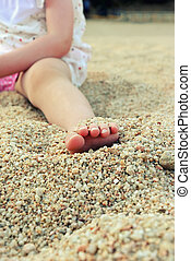 Close up toddler foot on a sandy beach
