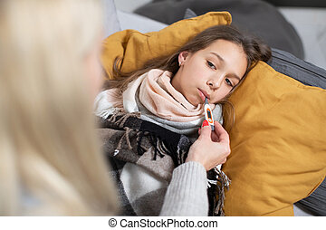 Close up top angle view of cute teen girl, with thermometer in mouth, lying on sofa or bed with scarf around neck, suffering from flu or tonsillitis, looking on her mother, checking temperature