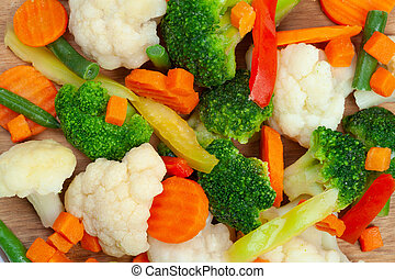 Close up top view of frozen mixed vegetables cauliflower, carrots, broccoli, sliced bell peppers lying on wooden cutting board