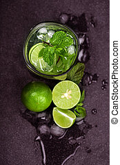 Close up top view or overhead shot of  the fresh mojito cocktail with fresh lime and mint leaf on black stone background