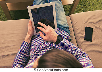 Close up top view photo of man sitting on sofa with tablet