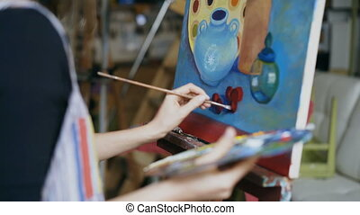 Close-up tracking shot of artist woman with brush painting still life picture on canvas in art-class