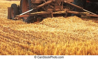 Close up tractor and dry yellow straw. Agriculture work.