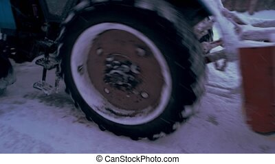 Close up tractor cleaning snow from road. Wheel tractor...