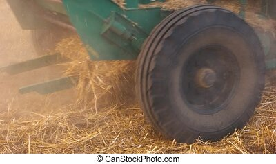 Close up tractor with straw. The tractor wheels on the huge...