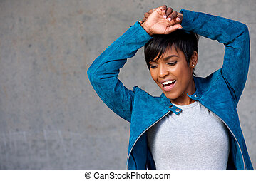 Close up trendy young black woman smiling against gray wall
