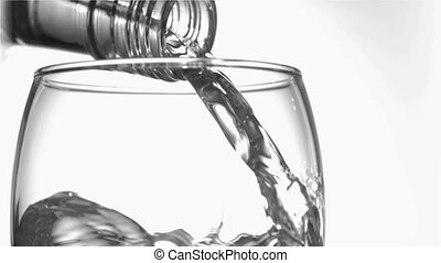 Close up, trickle of water in a super slow motion flowing of the glass bottleneck in a glass