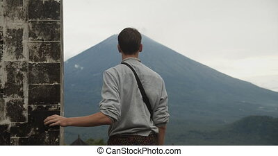Close up truck view of a man standing between the Gates of Heaven black stone pillars in Pura Penataran Agung Lempuyang temple and looking at Mount Agung volcano in Bali, Indonesia 4K