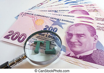 Close up Turkish lira with magnifying glass