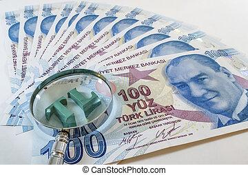Close up Turkish lira with magnifying glass