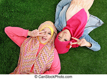 Close up two beautiful happy muslim woman lying on grass -...