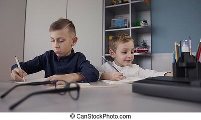 Close up. Two brothers of schoolchildren sit at the table in the white room and carry out a homework assignment in a copybook