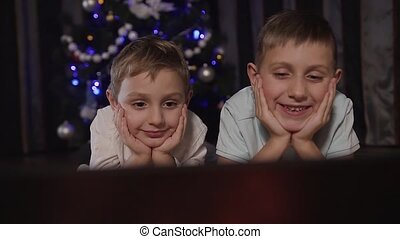 Close up. Two charming children look at something interesting on the laptop through the internet. Christmas evening, happy time, family
