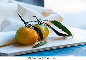 Close up two fresh tangerines with leaves on white