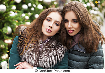 Two happy young women in winter street, outdoors