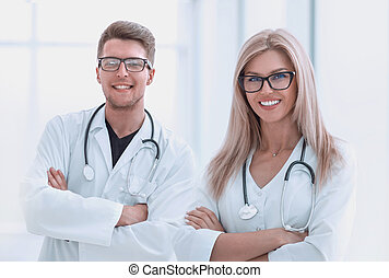 two medical doctors with stethoscopes standing in the hospital corridor