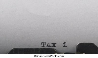 Close-up typing a text Tax invoice, old vintage typewriter with a sheet of paper.