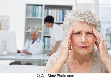 close-up, van, een, senior, patiënt, lijden, van, hoofdpijn, met, artsen, in, de, achtergrond, op, de, medisch kantoor