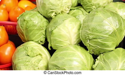 Close up video of a lot of great tasty fresh green cabbage swings lying on the counter before being sold on the market.