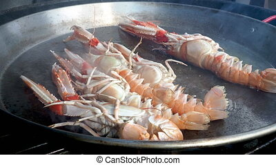 Close up video of fresh seafood cooking in paella pan - Chef...