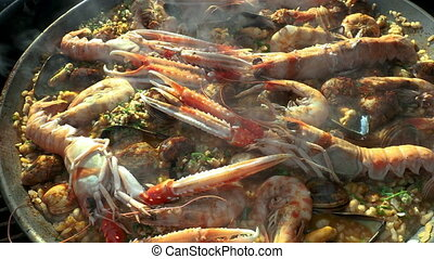 Close up video of fresh seafood cooking in paella pan - ...
