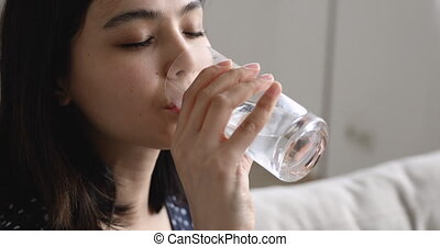 Close up view asian woman drinks glass of water - Close up ...