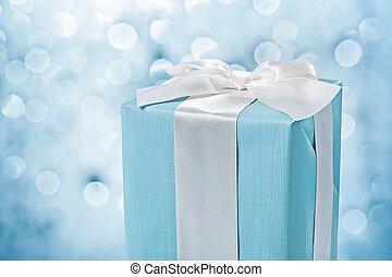 close up view blue gift box with white bow on blurred background