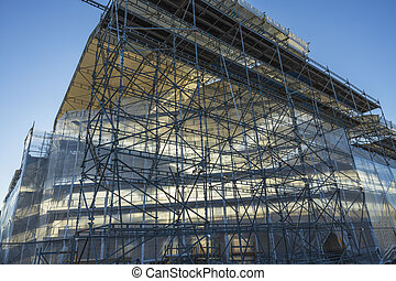 Close up view building under construction on blue sky background. Industry concept.