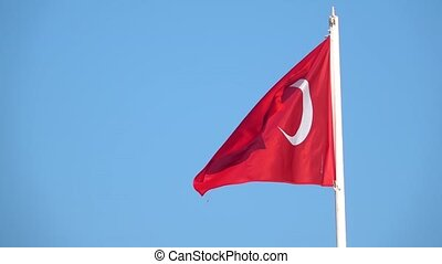 Close-up view flag of Turkey waving in the wind on a blue sky background without clouds, turkish symbol consists of a red leaf with a white crescent and a five-pointed star