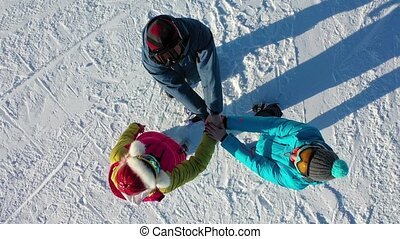 Close-up view from above of young people putting their hands together. Skiers and snowboarders with a stack of hands, demonstrating unity and teamwork, before descending the mountain.
