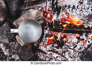 Close-up view from above with a mug of water standing in a fire on the coals and heated. Mocap for inserting information into the mug