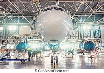 Close up view nose aircraft inside the aviation hangar, maintenance service.
