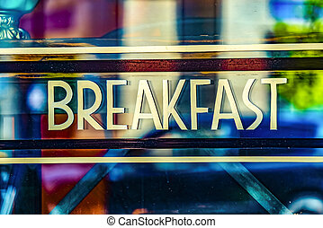 Close up view of a Breakfast sign against the glass wall of a restaurant