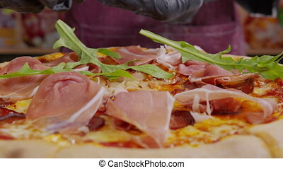 close up view of a chef sprinkling fresh cilantro on a cooked pizza. sprinkling a garnish on a freshly baked pizza. the process of making pizza. freshly baked pizza in restaurant. slow motion