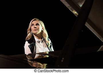 Close up view of a girl plays piano in the concert hall at scene