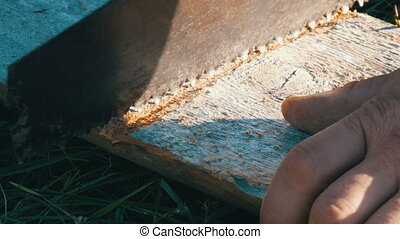 Close up view of a man sawing wood Board with hand saw and...