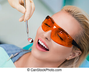 Close up view of a woman on teeth whitening procedure