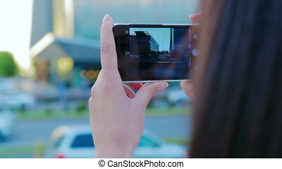 Close up view of a young girl taking pictures using smartphone