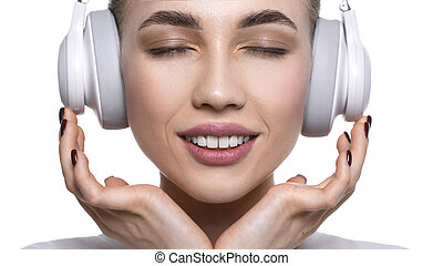 Close up view of a young woman listening to the music via headphones. Isolated on white