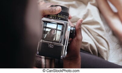 Close-up view of african man holding old photocamera, taking photo of woman near window. Multiracial couple on the bed.