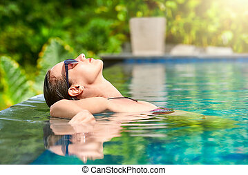 Close up view of an attractive young woman relaxing on a spa's swimming pool.